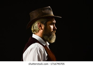 mature cowboy. detective acknowledgement or greeting. trilby hat. man in vintage style wide brimmed hat. Man with retro Hat. brutal bearded hipster in suit vest. mafia gentlemen club.