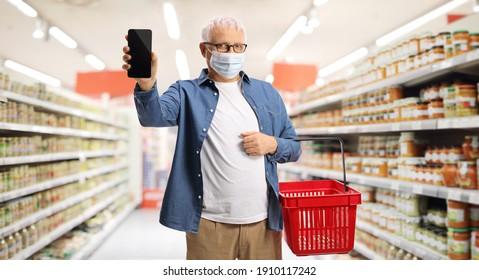 Reife Kunden in einem Supermarkt mit Gesichtsmaske und Handy