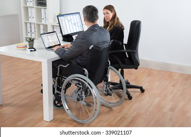 Mature Disabled Businessman And Businesswoman Working Together On Computer In Office