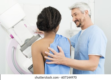 Mature Doctor Assisting Patient Undergoing Mammogram Test