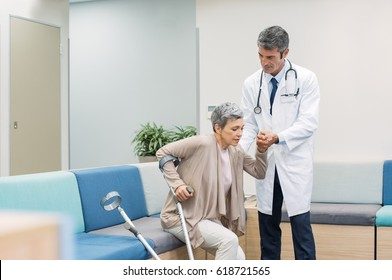 Mature doctor helping patient with crutches to get up in a hospital. Senior woman with broken leg taking support of doctor and crutches to get up at medical clinic.
