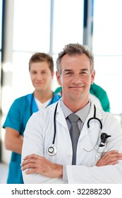 Mature doctor leading his team in hospital with copy-space