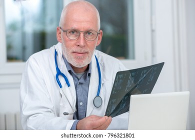 a mature Doctor looking at an x-ray in an office