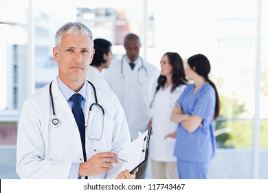 Mature doctor pointing seriously at something on his clipboard
