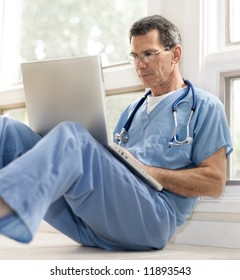 Mature doctor sitting on floor, leaning against wall, in blue scrubs, working on his laptop