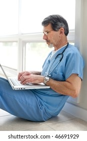 Mature doctor sitting on floor reviewing data on his laptop computer. Light and bright exposure.