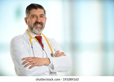 Mature doctor smiling with large window in background