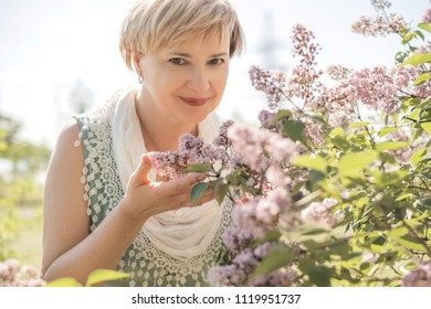 Mature elderly woman in dress enjoys union with nature, fresh air and flowers in garden. Sunny warm but windy weather