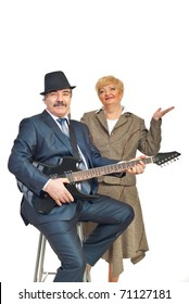 Mature elegant guitarist playing guitar and his wife smiling isolated on white background