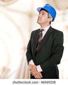 Mature engineer with blue hat looking up