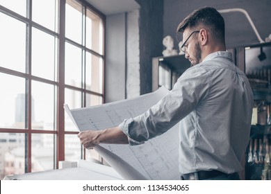 Mature engineer with a drawing indoors