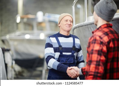 Mature engineer shaking hand of young colleague after discussing some details of teamwork