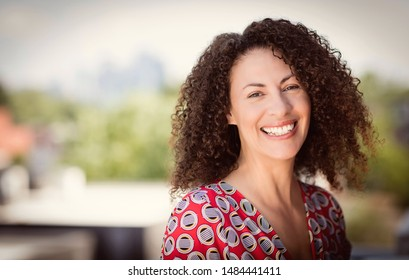 Mature Ethnic Woman Smiling At The Camera. She is outside on the roof of her house