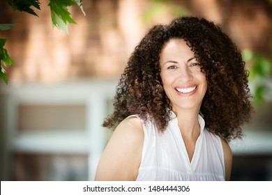 Mature Ethnic Woman Smiling At The Camera. She is outside in front of her house