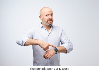 Mature european businessman impatiently pointing to his watch. Why are you late concept. I am waiting here for hours.
