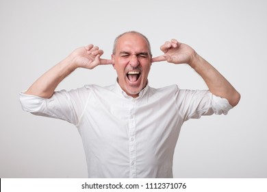 Mature european man closing his ears because of loud sound and noise. I do not want listen to you. Concept of facial negative emotion
