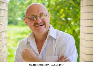 Mature European man in white shirt in eye glasses feeling happy and comfortable. A human with problem eyes enjoys life. Fun and joyful for every moment