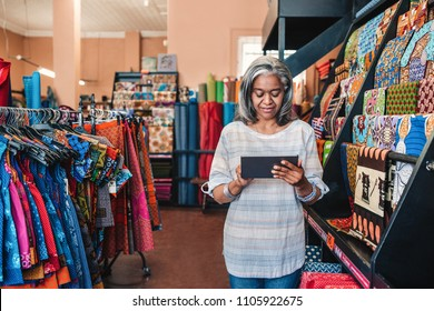 Mature fabric shop owner using a digital tablet while standing next to racks full of colorful cloths and textiles