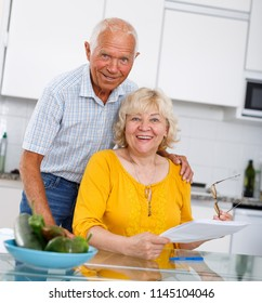 Mature family couple sitting at kitchen table with documents together