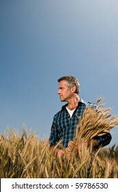 Mature farmer looking with satisfaction at his cultivated field with a bunch of ripe wheat after a working day