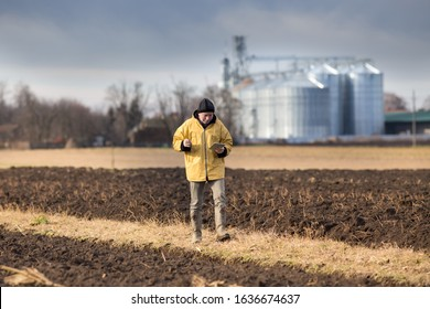 Mature farmer with tablet walking in field in winter time, with grain silos in background