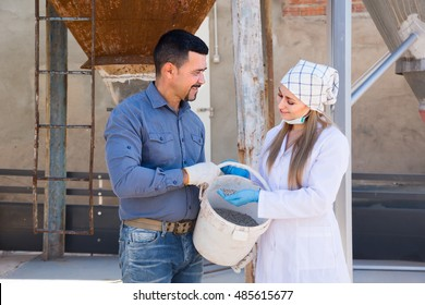 Mature farmer and woman in white coat holding bucket with pelleted food for hogs