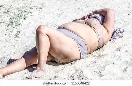 Mature fat woman sunbathing on the beach