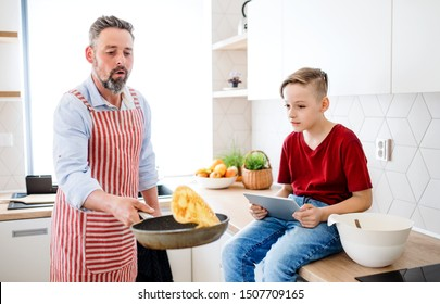 Mature father with small son indoors in kitchen, making pancakes.