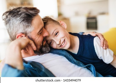 Mature father with small son sitting on sofa indoors, resting.