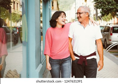 Mature father and young daughter having fun walking on the street