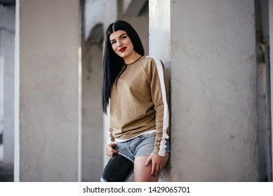 Mature female amputee personal trainer in crop top posing with confidence with prosthetic limb and foot against a wall hands on hips in power. Portrait. Inspiration for memes overcoming adversity