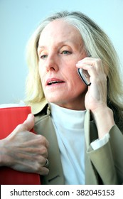 Mature female blond beauty talking on her cellphone.