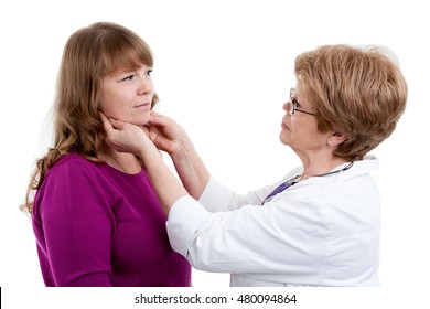 Mature female doctor checks the throat of a young female patient, isolated on white background