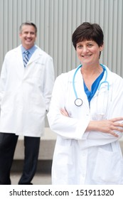 mature female doctor with colleague at hospital