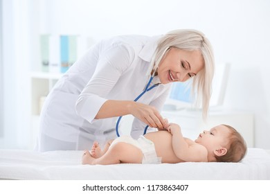 Mature female doctor examining baby boy in clinic