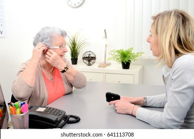 Mature female doctor hearing specialist in her office trying hearing aid equipment to a patient elderly senior woman