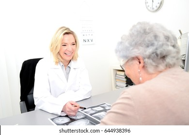 Mature female doctor in her office showing medical x-ray radiography to an elderly senior woman
