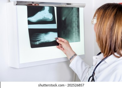 Mature Female Doctor Looking At Patients X-ray.