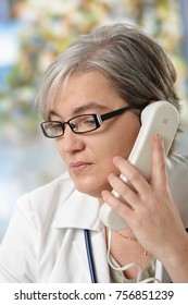 Mature female doctor on the phone, looking away, smiling