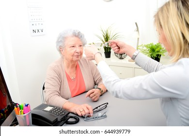 Mature female doctor ophthalmologist in her office trying eyeglasses to a patient elderly senior woman