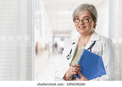 Mature female doctor standing on hospital corridor, holding clipboard, looking at camera, smiling.