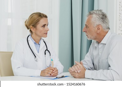 Mature female doctor talking with patient