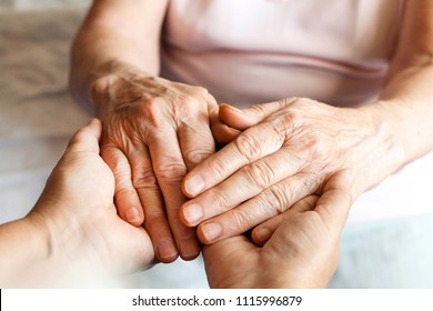 Mature female in elderly care facility gets help from hospital personnel nurse. Senior woman w/ aged wrinkled skin & care giver, hands close up. Grand mother everyday life. Background, copy space.