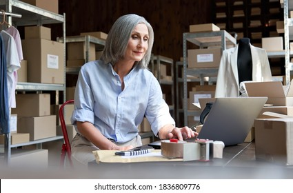 Mature female fashion seller using computer checking ecommerce clothing store orders. Older middle aged business woman entrepreneur working on laptop preparing online shipping delivery parcels boxes.