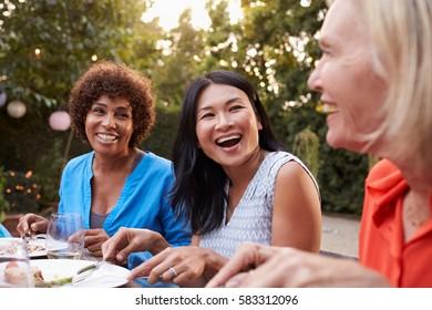 Mature Female Friends Enjoying Outdoor Meal In Backyard