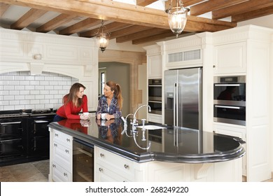 Mature Female Friends Standing In New Luxury Fitted Kitchen And Talking
