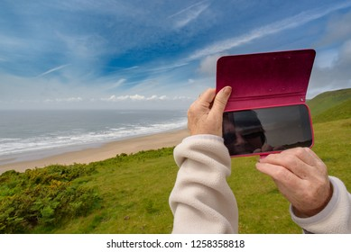 Mature female (hands only visible) taking a photograph of a seascape on her mobile phone, Rhossili Bay, Gower, South West Wales, UK.