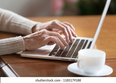 Mature female hands typing text on keyboard, senior elderly business woman working on laptop, old or middle aged lady using computer concept writing emails, communicating online, close up view