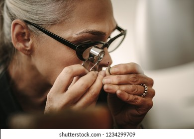Mature female jeweler looking at stone through loupe to inspect it. Close up of senior jewelry maker looking at the gem while working at workshop.