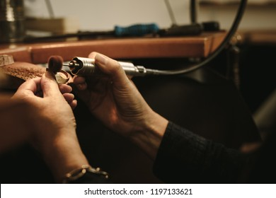 Mature female jeweler polishing a gold ring at workbench. Goldsmith making a ring at her work shop using tools. Close up of hands of jewelry maker using polishing machine.
